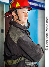 Side View Of Confident Firefighter At Fire Station - Side...