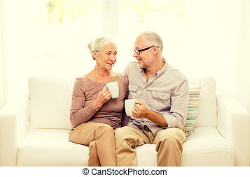 happy senior couple with cups at home - family, relations,...