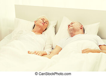 happy senior couple lying in bad at home - family, bedtime,...