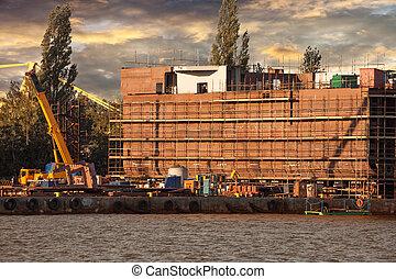Shipyard - Ship under construction in shipyard at sunrise.