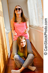 Two funny happy teenage girls having fun riding on back -...