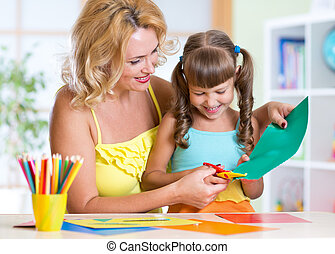 little girl and mother cutting paper with scissors