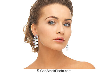 woman wearing shiny diamond earrings - close-up of beautiful...