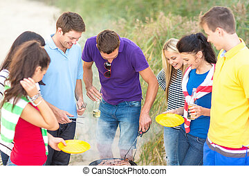 group of friends having picnic on beach - food, eating,...