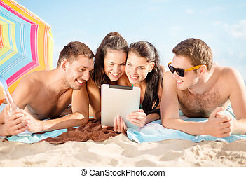happy friends with tablet pc on beach - summer holidays,...