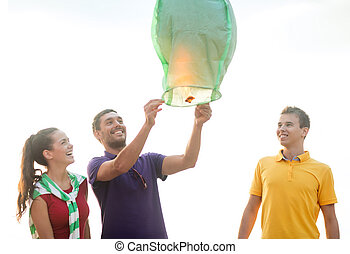 happy friends with chinese sky lantern on beach