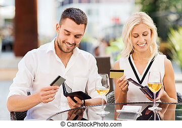 couple with credit cards paying bill at restaurant - date,...