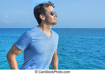 Out on the water - Handsome muscular Caucasian man wearing...