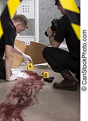 Crime scene investigation - Young police officers during...