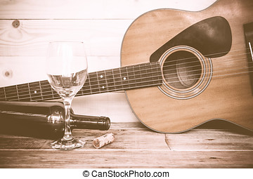 vintage Guitar with wine bottle and glass on the old wood...