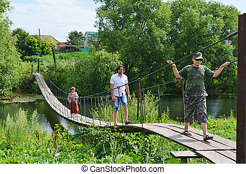 People walk on suspension bridge over the river - Three...
