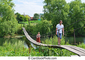 People walk on suspension bridge over the river - two people...