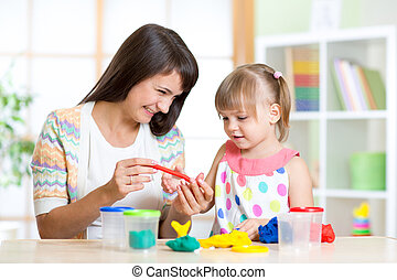 mother teaches her child to play with colorful play clay...