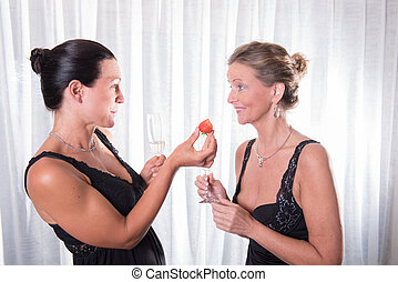 two attractive women - one is offering strawberry to her friend
