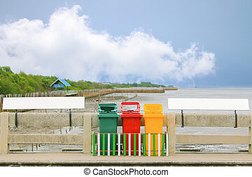Colorful bin between signage on blue sky background -...