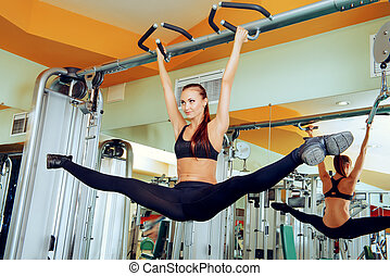 splits - Slender girl doing stretching exercises at the gym...