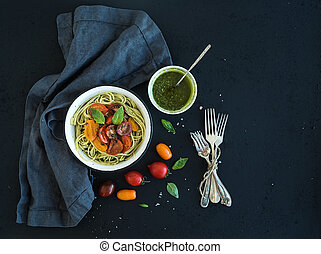 Pasta spaghetti with pesto sauce, basil, slow-roasted cherry-tomatoes in rustic metal bowl on dark grunge backdrop, top view