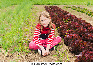 Cute little girl playing in a garden