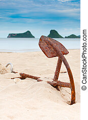 Rusty Anchor on the beach with sea as background