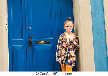 Fashion portrait of a cute little girl, wearing warm knitted cardigan, standing next to bright blue door