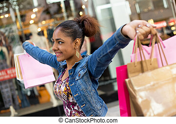 shopping girl - young woman holding shopping bags with arms...