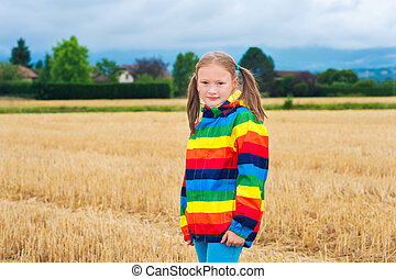 Adorable little girl playing in a field, wearing rainbow...