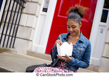 take-away - young woman eating a chinese take-away on her...