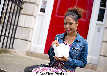 take away - young woman eating a chinese take-away on her...