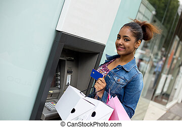 atm - young woman withdrawing cash at the atm
