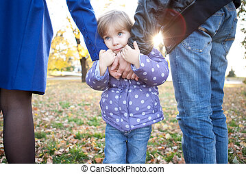 Sad little girl holds parents hands