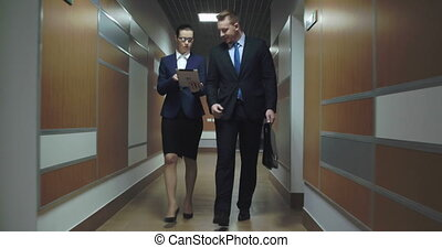 Project Partners - Businesswoman and businessman walking to...