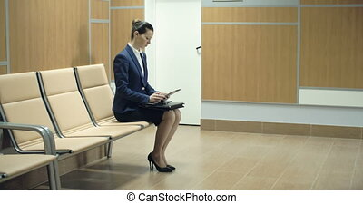 Waiting for Job Interview - Woman in formal suit using...