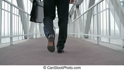 Keep Moving Forward - Low section of businessman walking...