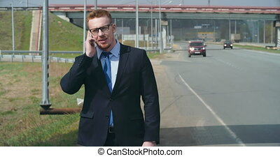 Trying to Hitch a Lift - Young businessman standing at road...