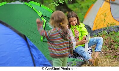 Family hike - The deciduous forest is a campground Two girls...