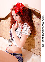 Pensive pinup girl with gorgeous red hair sitting on sofa