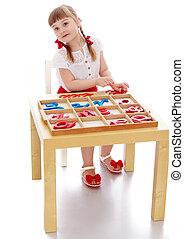 The girl in the Montessori environment - little girl with...