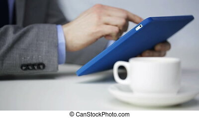 close up of man with tablet pc drinking coffee - business,...