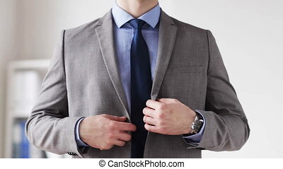 close up of man in suit fastening button on jacket