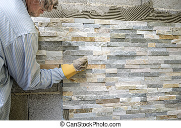 Older man decorating a wall with ornamental tiles pressing...