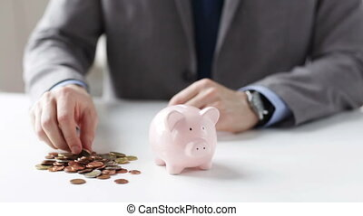 close up of man putting coins into piggy bank - people,...