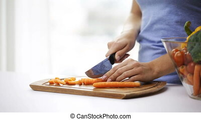 close up of young woman chopping carrot at home - healthy...