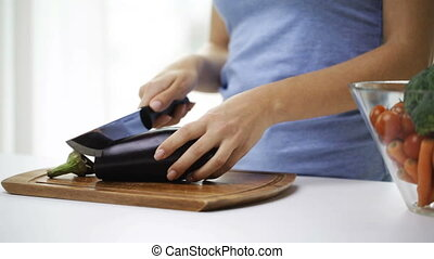 close up of young woman chopping eggplant at home - healthy...