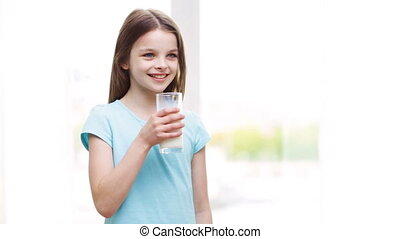 happy smiling little girl drinking milk at home - people,...