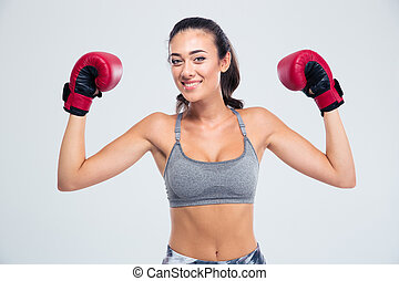 Fitness woman standing with boxing gloves in victory pose -...