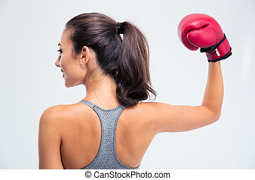Woman standing with boxing gloves in victory pose - Back...