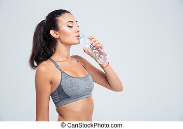 Beautiful sports woman drinking water - Portrait of a...