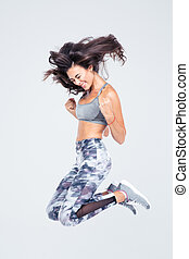 Cheerful fitness woman jumping - Full length portrait of a...
