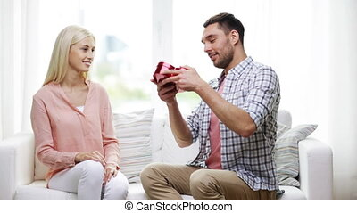 man giving woman red heart shaped gift box - relationships,...