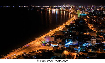 view of night city shore in lights with coast road traffic -...